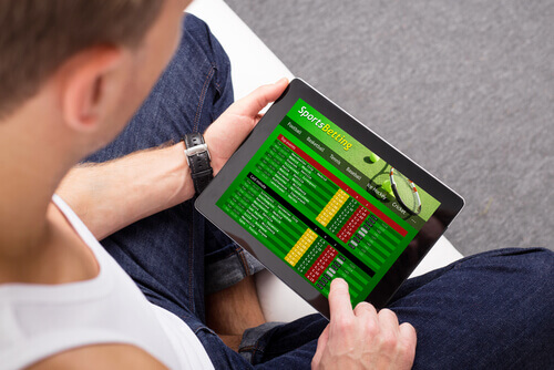 man on iPad - sports betting Australia
